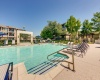 View of Resort Style Pool, Showing Waterfeature, Sundeck, Trees, and Apartment Building Exterior at Toscana at Valley Ridge Apartments